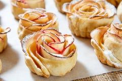 自创饼干用苹果以的形式在烘烤纸上升了 库存照片