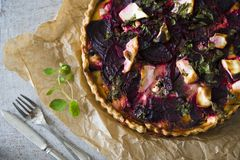 自创饼用甜菜和乳酪在葡萄酒桌上,在一把老匙子和叉子旁边 库存图片