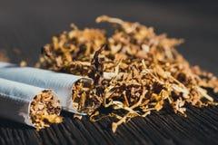 自创香烟和烟草在棕色木桌上 免版税库存图片