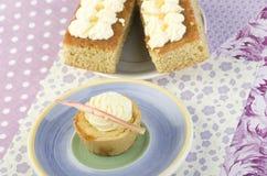 自创香草杯形蛋糕和两块蛋糕与香草奶油的 库存照片