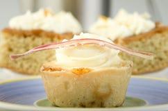 自创香草杯形蛋糕和两块蛋糕与香草cre的 免版税图库摄影