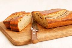 自创香蕉面包和刀子在厨房切板 库存图片