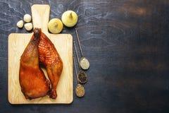 自创鸡腿在一串烤肉和香料油煎了在一个切板在黑背景 顶视图从上面 复制空间 免版税库存图片