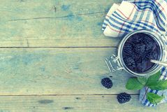 自创黑莓在土气木tabl的一个玻璃瓶子阻塞 库存图片