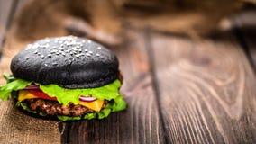 自创黑汉堡用乳酪 乳酪汉堡用在黑暗的木背景的黑小圆面包 图库摄影
