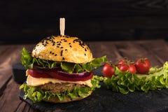 自创素食汉堡用炸肉排、蕃茄、乳酪、蔬菜沙拉和紫洋葱在黑暗的木背景 库存图片
