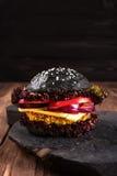 自创素食者黑色燕麦粥汉堡用一道炸肉排、蕃茄、乳酪、黑暗的沙拉和紫洋葱在土气木桌上 库存图片