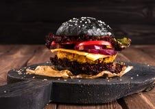 自创素食主义者黑色鸡豆汉堡用一道炸肉排、蕃茄、乳酪、黑暗的莴苣和紫洋葱在土气木 免版税库存照片