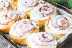 自创Cinnabon小圆面包用桂香和奶油在白色板材在木桌和餐巾上 m r 免版税图库摄影