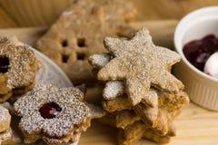 自创linzer曲奇饼用果酱,搽粉,用不同的形状,在木委员会,关闭  免版税库存照片