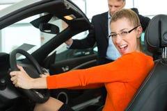 自动位子的少妇在售车行中 库存图片