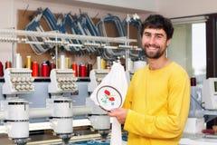 自动刺绣机器的微笑的操作员 免版税库存照片