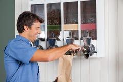 从自动售货机的人买的咖啡  免版税库存图片