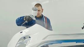 自动在汽车前保险杆的画家喷洒的白色油漆在特别摊 库存图片
