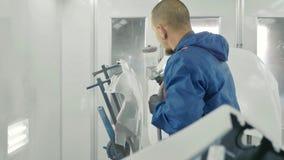 自动在汽车备用防御者的画家喷洒的白色油漆在特别摊 库存图片