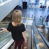 自动扶梯的妇女在机场大厅 有葡萄酒的夫人 免版税库存照片