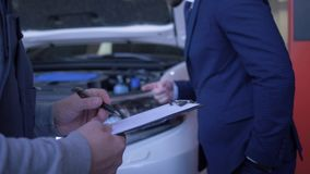 自动技术员写从客户的任务关于汽车检查和修理有敞篷的开放在车间 股票视频