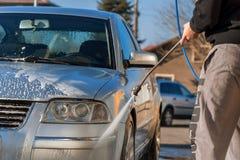 自动服务的工作者由水水管洗涤豪华汽车, b 免版税库存照片