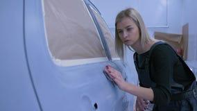 自动画家铺沙的汽车在油漆房间的油漆用手和微笑在修理工作期间 股票录像