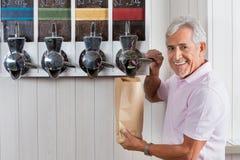 从自动贩卖机的老人买的咖啡豆 免版税库存照片