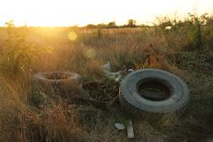 自发转储被放弃的轮胎和家庭垃圾 在土路一边的垃圾堆 回收垃圾的问题 免版税库存图片
