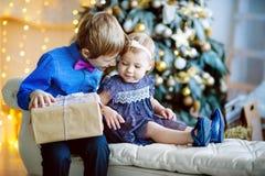 自圣诞前夕的家庭在壁炉 打开Xmas礼物的孩子 孩子在与礼物盒的圣诞树下 免版税库存照片
