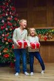 自圣诞前夕的家庭在壁炉 打开Xmas礼物的孩子 免版税库存图片