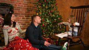 自圣诞前夕的家庭在壁炉 打开Xmas礼物的父母和小孩 有礼物盒的孩子 居住 股票视频