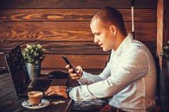 自己经营的愉快的人与膝上型计算机和一个巧妙的电话一起使用 库存照片