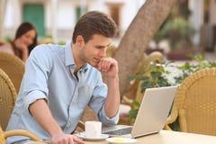 自己经营的人与一台膝上型计算机一起使用在餐馆 库存照片