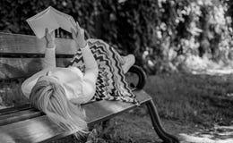 自我改善的时刻 妇女花费与书的休闲 夫人喜欢读 读的女孩户外,当放松时 免版税库存图片