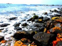 自然五颜六色的彩虹石头,惊人的蓝色海 免版税库存照片