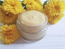 自然化妆奶油,在白色木背景的黄色菊花 免版税库存图片
