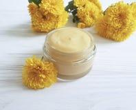 自然化妆奶油,在白色木背景的hygieneyellow菊花 库存照片