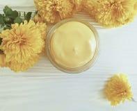自然化妆玻璃奶油,在白色木背景的hygieneyellow菊花 图库摄影