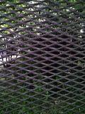 自然和绿叶在金属棒后在一个夏日 免版税库存照片