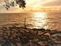 自然和美好的日落在椰树小屋海湾米里沙捞越马来西亚 免版税库存图片