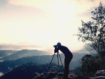 自然在三脚架的摄影师逗留在山顶和认为 多小山有雾的风景 库存照片