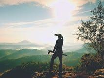 自然在三脚架的摄影师逗留在山顶和认为 多小山有雾的风景 免版税库存图片