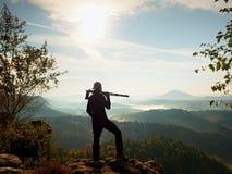 自然在三脚架的摄影师逗留在山顶和认为 多小山有雾的风景 库存图片