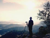自然在三脚架的摄影师逗留在山顶和认为 多小山有雾的风景 免版税图库摄影