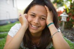 自然地说谎在与愉快的微笑的草的美丽的十几岁的女孩。 免版税库存图片