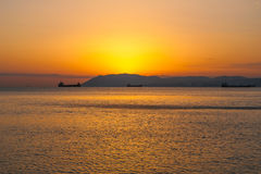 自然夏天海日落 土地船和小条剪影天际的 库存照片