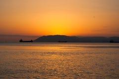 自然夏天海日落 土地船和小条剪影天际的 免版税库存图片