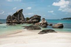 自然岩层在海和在一个白色沙子海滩在勿里洞岛海岛,印度尼西亚 库存图片
