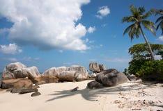 自然岩层在海和在与一棵棕榈树的白色沙子海滩在勿里洞岛海岛 免版税库存图片
