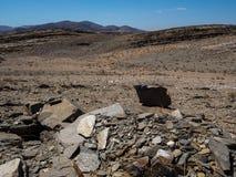 自然岩石山烘干了纳米比亚沙漠多灰尘的风景地面有分裂的页岩片断、其他石头和沙漠植物的 库存图片