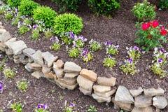 自然岩石护墙在庭院里 免版税库存图片