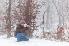 自然摄影师在冬天森林里 库存照片