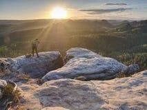 自然摄影师有照相机的举行三脚架 日出的人 图库摄影